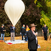 Balloon launch ceremony with Dr Ady James speaking and the ballon in the background.