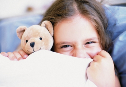 girl in bed under covers with teddy bear