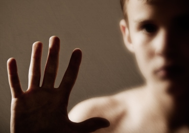 image of a boy with his hand up against a pane of glass