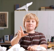 Boy throwing a paper plane in a classroom.
