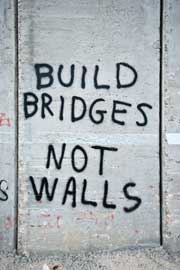 Wall graffitied with the words BUILD BRIDGES NOT WALLS.