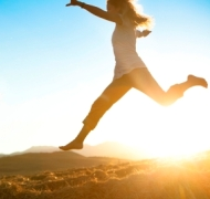 Women leaping across a field with sunshine behind her.