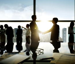 Silhouette of business executives shaking hands with sunset through glass windows