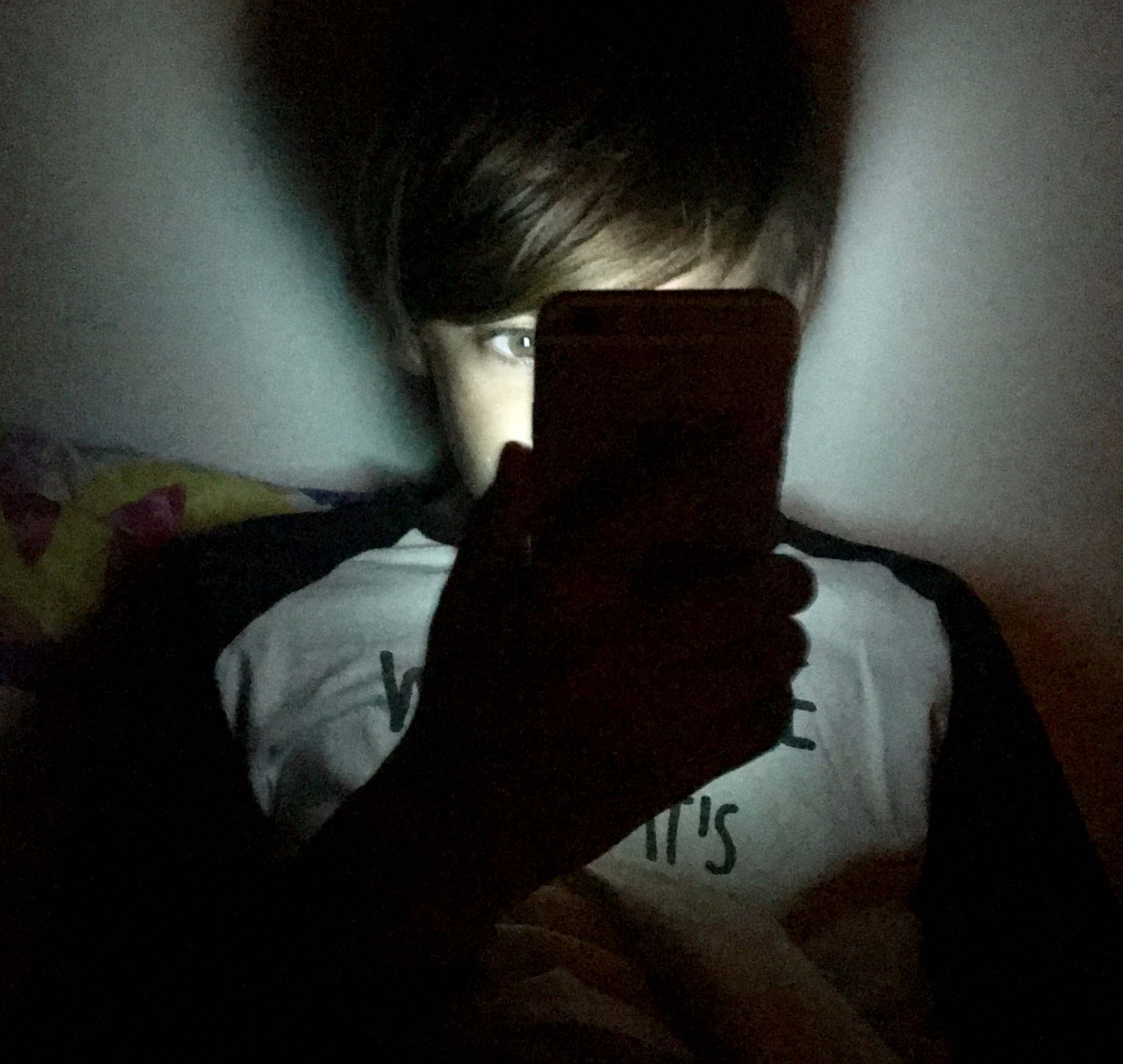 Boy using mobile phone at night