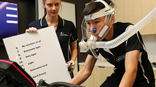 Exercise sports science student Lucy Cleggett with jockey Gary Lo, who is having his respiratory physiology analysed as part of a unique UniSA study. Photo by Sarah Reed, The Advertiser.