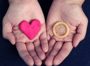 Two hands showing a stone heart and a condom