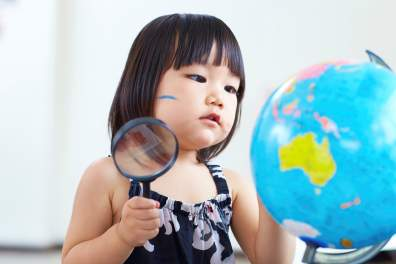 Girl exploring globe with magnifying glass