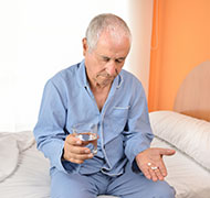 Elderly man taking his pills