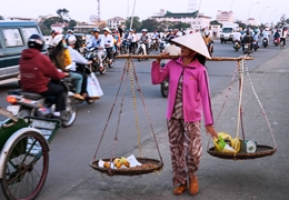 Street scene in Hue Vitenam showing cyclists and people on foot carrying goods