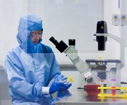 Researcher wearing a clean room suit in the cell therapy manufacturing lab.