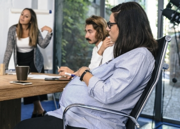 Pregnant woman discusses strategy with her research team