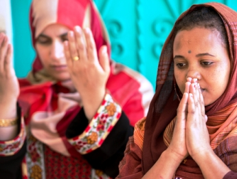 A Muslim woman and a Christian woman both in prayer