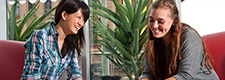 Two students sit in front of potted plants
