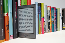 A kindle sitting amongst the books on a shelf