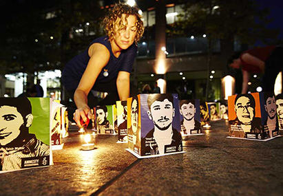Woman lights candle for Syria