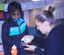 Project officer Debra Gent handing out fish oil capsules as part of a project in NT schools
