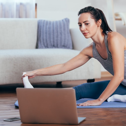Woman doing yoga online at home.