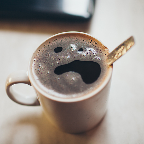 sick face on froth of coffee