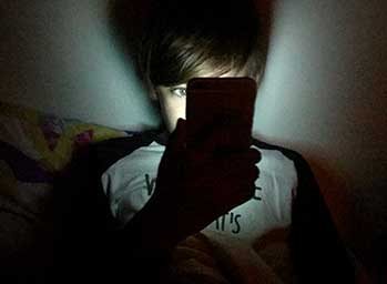Boy in bed using a mobile phone at night