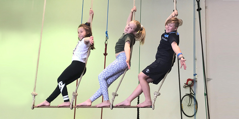 Gracie, 8, Georgina, 10 and Akira, 9 hanging on the trapeze at Cirkidz Circus school, Adelaide.