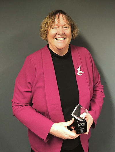 Associate Professor Jane Warland holding her Excellence in Bereavement Care Award.