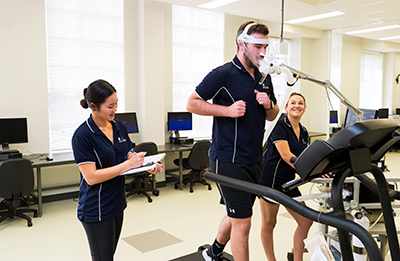 Human Movement, Occupational Therapy and Physiotherapy students Ashleigh Clark, James Fox and Katy Phan in the Exercise Physiology laboratory.=